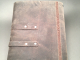 gray and light brown hand stitched leather journal with two snaps