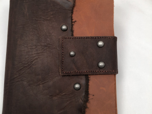 Dark brown and tan leather journal with button closure